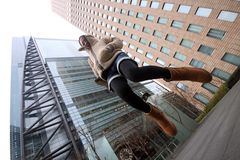 Young Japanese girl jumping in front of buildings Stock Photography