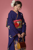 Young Japanese Girl in Kimono. A portrait of a beautiful young Japanese girl in a blue kimono for her coming of age ceremony on her 20th birthday royalty free stock images