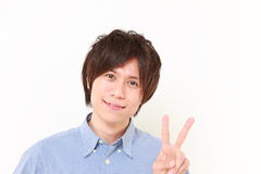 Young Japanese man showing a victory sign Royalty Free Stock Images