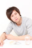 Young Japanese man suffers from a neurosis. Studio shot of young Japanese man on white background Stock Images