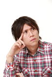 Young Japanese man worries about something. Studio shot of young Japanese man on white background stock photos