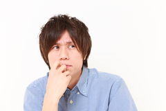 Young Japanese man worries about something. Studio shot of young Japanese man on white background Royalty Free Stock Photo