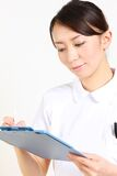 Young Japanese nurse with clinical record Royalty Free Stock Photo