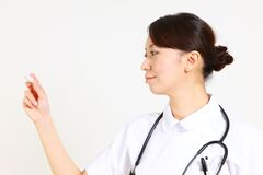 Young Japanese nurse with clinical thermometer Stock Image