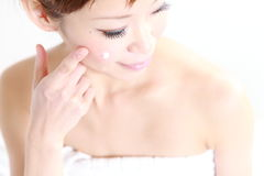 Young Japanese woman applying cream on her face Royalty Free Stock Images