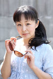 Young japanese woman with brown sunglasses. Portrait of young japanese woman hand holding brown sunglasses Stock Images