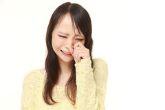 Young Japanese woman cries. Studio shot of young Japanese woman's portrait on white background Royalty Free Stock Photography