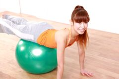 Young Japanese woman doing exercise with fitness ball Stock Images
