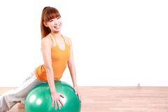 Young Japanese woman doing exercise with fitness ball Royalty Free Stock Photos