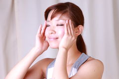 Young Japanese woman doing a self face massage  Royalty Free Stock Photography