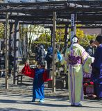 Young Japanese woman dressed in yellow Kimono, with small boy dancing in blue kimono, Asakusa, Japan, 2018 stock photography