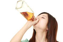 Young Japanese woman drinking straight from a bottle Royalty Free Stock Photography