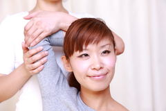 Young Japanese woman getting chiropractic Royalty Free Stock Image