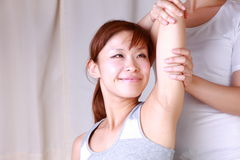 Young Japanese woman getting chiropractic Stock Image