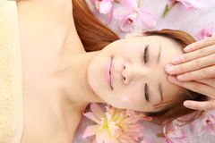 Young Japanese woman getting a face massage Stock Photography
