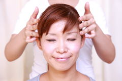 Young Japanese woman getting a head massage  Royalty Free Stock Photography