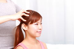 Young Japanese woman getting a head massage Stock Photography