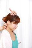 Young Japanese woman getting a neck massage  Royalty Free Stock Images
