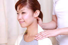 Young Japanese woman getting a neck massage  Royalty Free Stock Photography