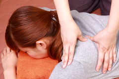 Young Japanese woman getting a shoulder massage  Royalty Free Stock Photography