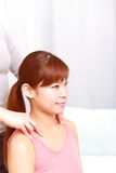 Young Japanese woman getting a shoulder massage  Royalty Free Stock Photos