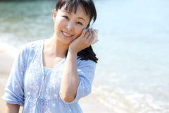 Young japanese woman listening seashell. Young japanese beautiful girl listening seashell at the beach Stock Photo