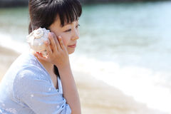 Young japanese woman listening seashell. Young japanese beautiful girl listening seashell at the beach Royalty Free Stock Images