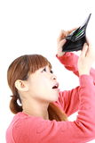 Young Japanese woman looking at her empty wallet Stock Photo