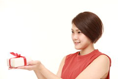Young Japanese woman offering a gift Royalty Free Stock Photos