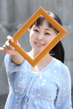 Young japanese woman with photo frame. Portrait of young japanese woman hand holding photo frame Royalty Free Stock Photos
