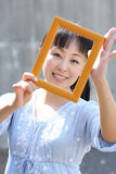 Young japanese woman with photo frame. Portrait of young japanese woman hand holding photo frame Stock Image