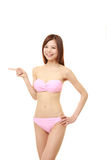 Young Japanese woman in a pink bikini presenting and showing something. Studio shot of young Japanese woman on white background royalty free stock photography