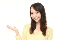 Young Japanese woman presenting and showing something Royalty Free Stock Images