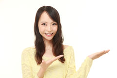 Young Japanese woman presenting and showing something Royalty Free Stock Photography