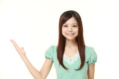 Young Japanese woman presenting and showing something Royalty Free Stock Photos
