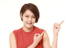 Young Japanese woman presenting and showing something Royalty Free Stock Photo