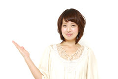 Young Japanese woman presenting and showing something Royalty Free Stock Image