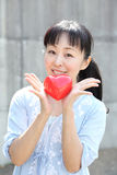 Young japanese woman with red heart. Portrait of young japanese woman hand holding red heart Stock Photo