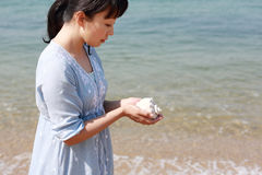 Young japanese woman with a seashell. Young japanese beautiful girl hand holding a seashell at the beach Royalty Free Stock Photo