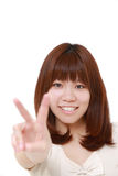 Young Japanese woman showing a victory sign Royalty Free Stock Photos