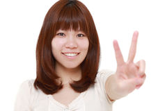 Young Japanese woman showing a victory sign Royalty Free Stock Photography