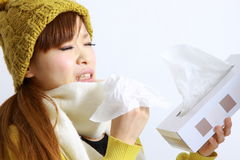 Young Japanese woman sneezing into tissue Stock Photos