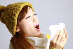 Young Japanese woman sneezing into tissue Royalty Free Stock Photo