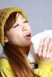 Young Japanese woman sneezing into tissue Royalty Free Stock Photography