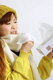 Young Japanese woman sneezing into tissue Royalty Free Stock Images