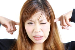 Young Japanese woman suffers from noise Royalty Free Stock Images