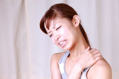 Young Japanese woman suffers from stiff neck Royalty Free Stock Photo