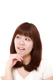 Young Japanese woman thinks about something. Studio shot of young Japanese woman on white background Royalty Free Stock Images