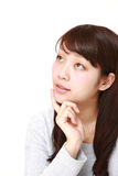 Young Japanese woman thinks about something. Studio shot of young Japanese woman on white background Royalty Free Stock Photo