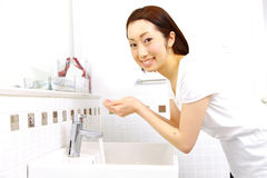 Young Japanese woman washes her face in lavatory Stock Images